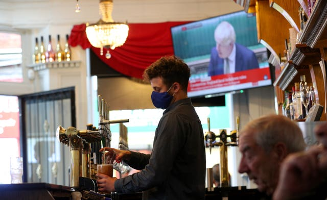 A member of staff pours a drink in the Richmond pub in Liverpool as Prime Minister Boris Johnson reads a statement on television (Peter Byrne/PA)
