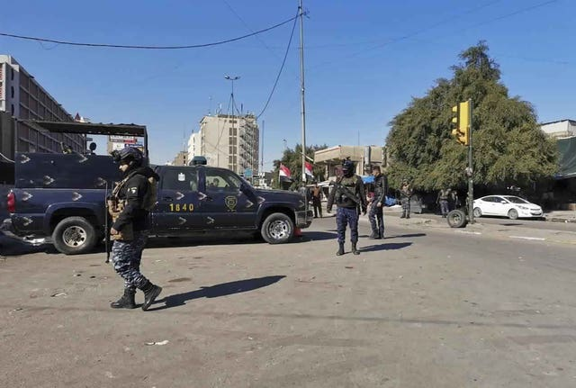 Security forces gather at the site of a deadly bomb attack in Baghdad's bustling commercial area