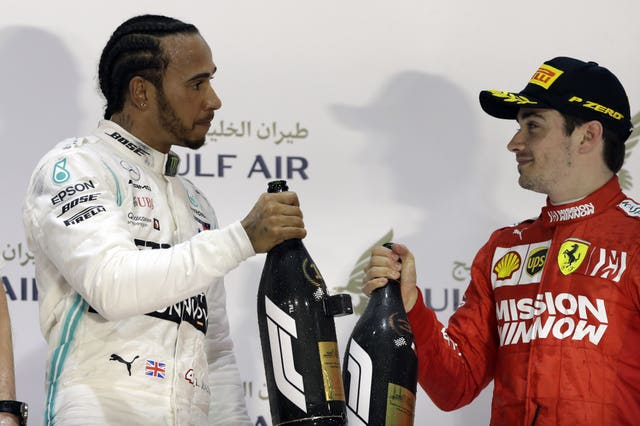 Mercedes driver Lewis Hamilton celebrates with third placed Ferrari driver Charles Leclerc after winning the Bahrain Grand Prix .