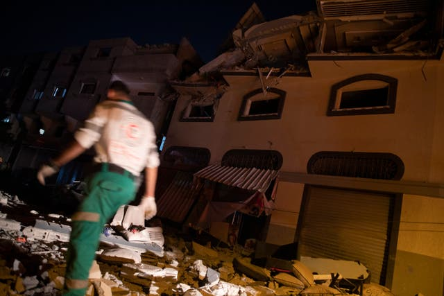 Palestinians check the damage caused by Israeli missile strikes in Gaza City