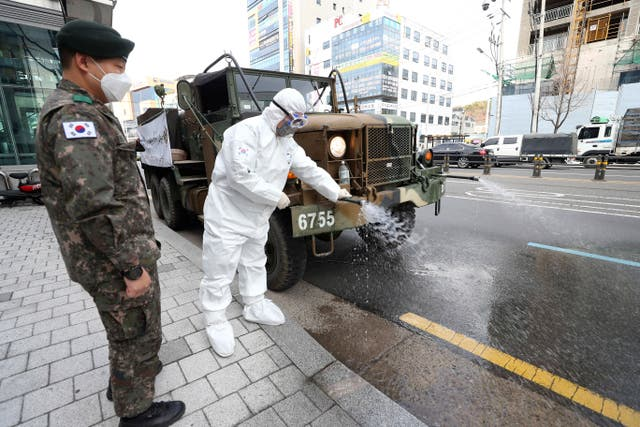 A South Korean soldier wearing a protective suit sprays disinfectant to prevent the spread of Covid-19 on a street in Daegu