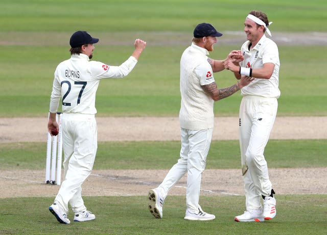 England's Stuart Broad, right, celebrates with Ben Stokes and Rory Burns