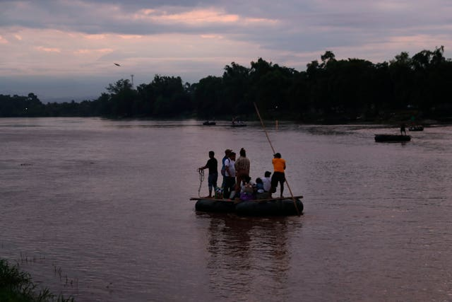 Migrants travel from Guatemala to Mexico on a raft