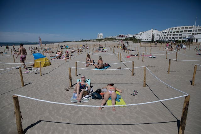 Sunbathers lie in an area marked to enforce social distancing measures in La Grande Motte, southern France (Daniel Cole/AP)