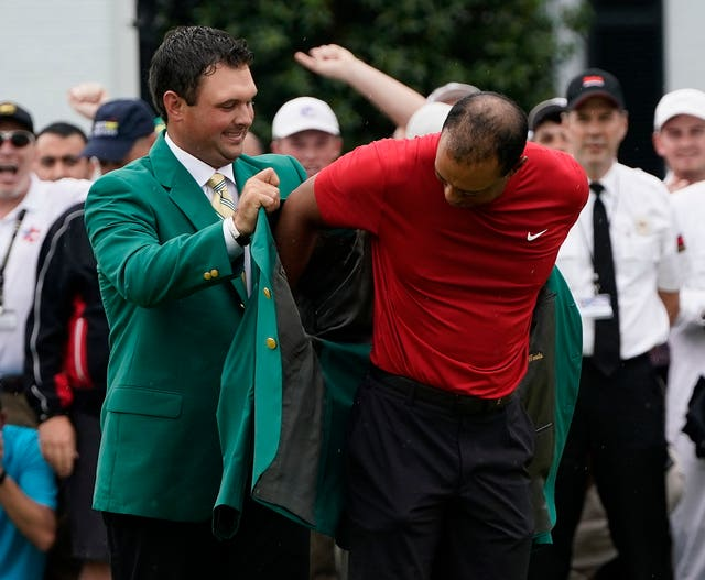 Patrick Reed, the 2018 Masters champion, helps Woods with his Green Jacket