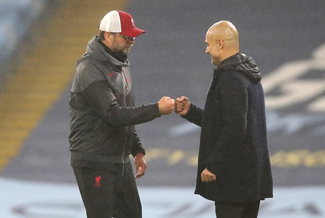 Jurgen Klopp, left, and Pep Guardiola bump fists