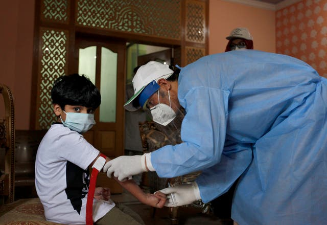 A health worker takes the blood sample of a boy during door-to-door testing and screening facility for coronavirus (Anjum Naveed/AP)