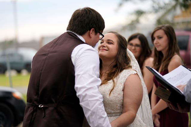 Emily and Taylor Pascale kiss after exchanging vows at their wedding outside the home of Taylor's parents in Grand Lake, Louisiana
