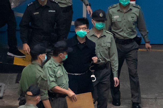 Activist Joshua Wong is escorted by officers to a prison van