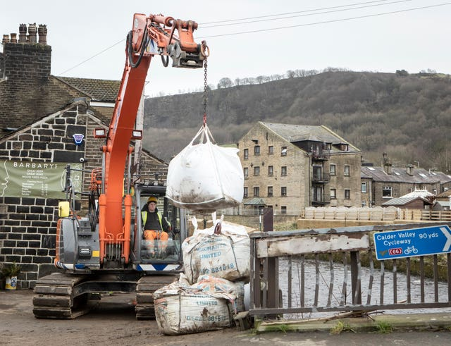 Workers construct flood defences in Mytholmroyd in the Upper Calder Valley, West Yorkshire