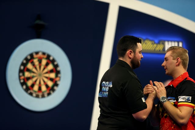 Luke Humphries (left) consoles Dimitri Van den Bergh after his victory