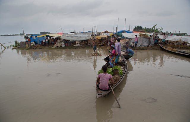 Flood-affected villagers travel on a boat as others take shelter on a highland in Katahguri village along the river Brahmaputra, east of Gauhati, India
