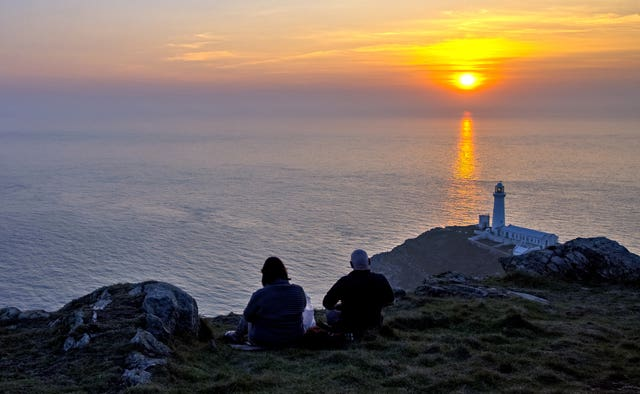 People watch the sun set behind South Stack lighthouse on Anglesey