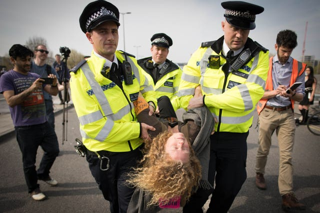 Police carry a climate activist away on Waterloo Bridge