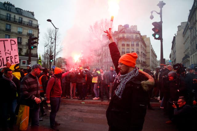 A protester holds a flare during a demonstration in Paris