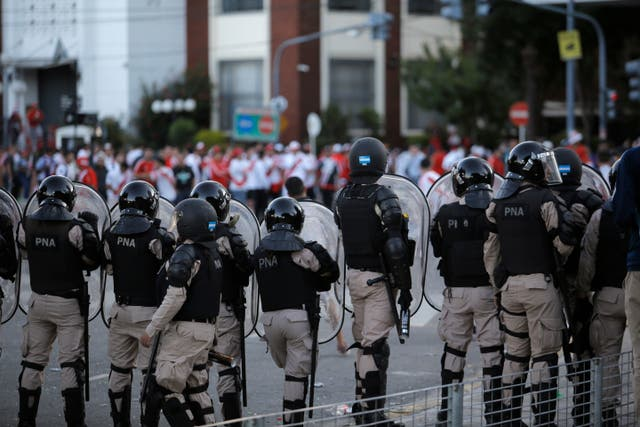 River Plate fans are confronted by riot police outside the stadium (Sebastian Pani/AP).