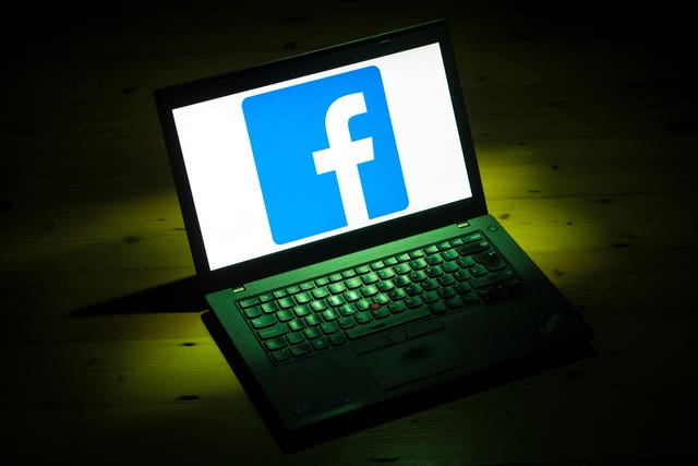 The Facebook logo displayed on a laptop
