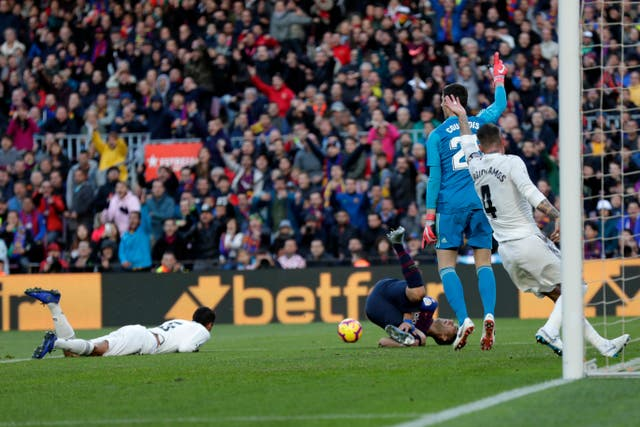 Barcelona appeal for a penalty after Luis Suarez goes down under a challenge from Real defender Raphael Varane