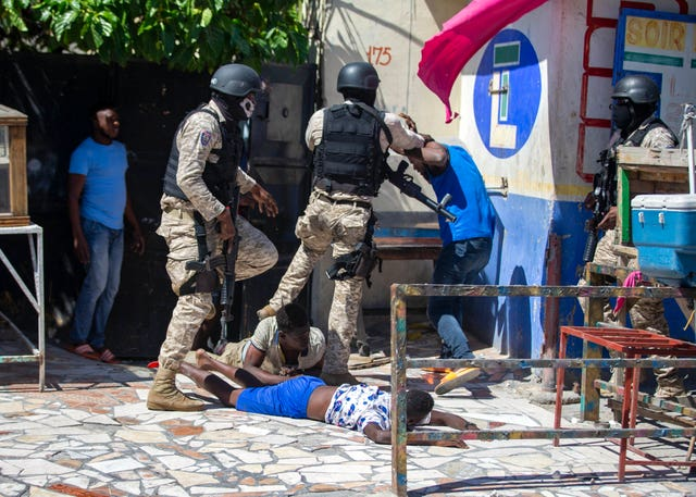 Police officers detain demonstrators during a protest to demand the resignation of Haitian President Jovenel Moise (Dieu Nallo Chery/AP)