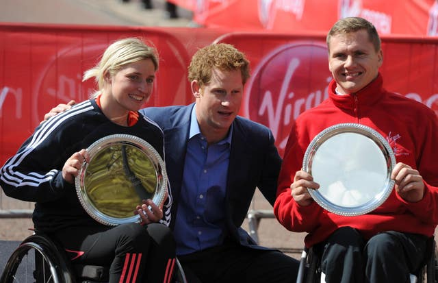 Prince Harry poses with Great Britain's Shelly Woods and David Weir after their victories in the wheelchair races in 2012