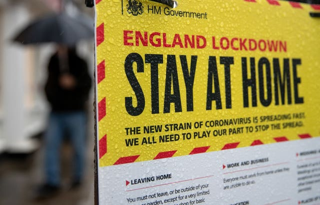 People walk past a Government sign warning people to stay at home