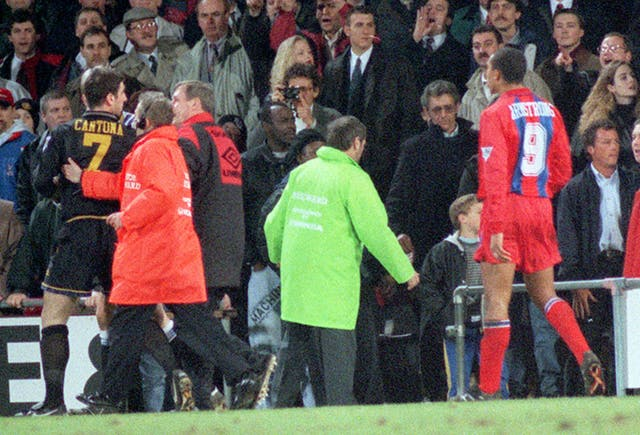 Cantona is escorted off the pitch after lunging at a fan in the crowd at Selhurst Park