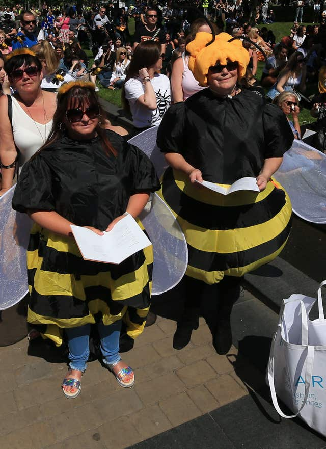 Two women in bee costumes in Cathedral Gardens, as they watch on screen the Manchester Arena National Service of Commemoration (Peter Byrne/PA)