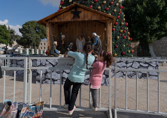 Palestinian children look at the Nativity scene in Manger Square (Nasser Nasser/AP)