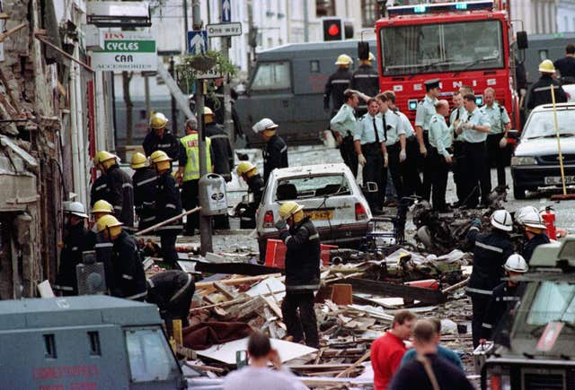 Police officers and firefighters inspecting the damage caused by a bomb explosion in Market Street, Omagh, in 1998