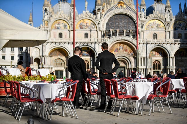 Waiters wait for customers in a restaurant at St Mark's Square in Venice