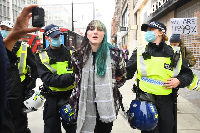 Police detain a woman during an anti-lockdown protest at Oxford Circus