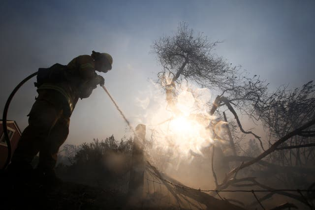 A firefighter battles a wildfire near a ranch in Simi Valley, California