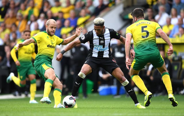 Teemu Pukki (left) and Newcastle's Joelinton (centre) battle for the ball