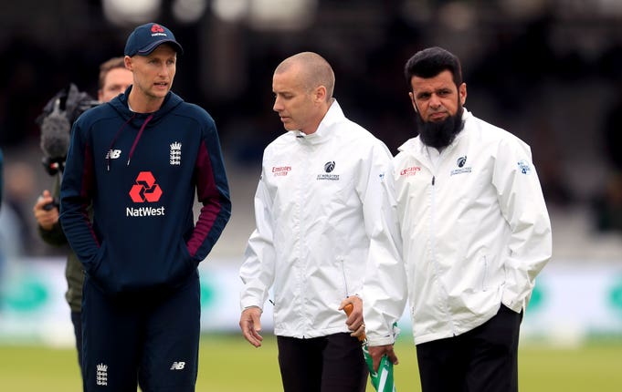 Umpires Aleem Dar and Chris Gaffaney (centre) speak to Joe Root during a pitch inspection