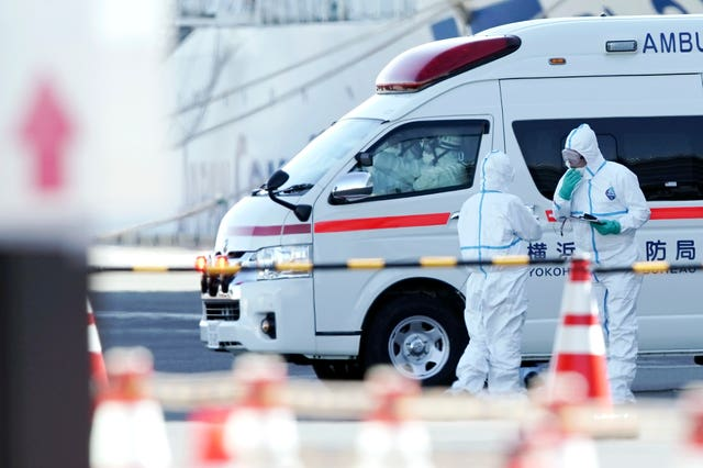Officials in protective suits near the cruise ship Diamond Princess (Eugene Hoshiko/PA)
