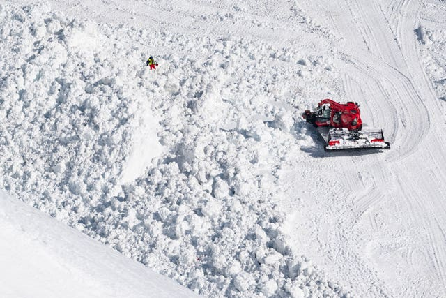 Rescue crews work on the avalanche site in the ski resort of Crans-Montana, Switzerland