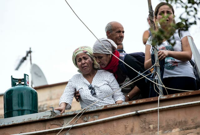 A woman cries as she stands with others on the roof of an abandoned school on the outskirts of Rome before being evicted