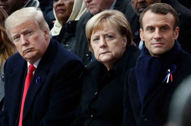 German Chancellor Angela Merkel and President Donald Trump attend a commemoration ceremony for Armistice Day in 2018 with France's President Emmanuel Macron (Benoit Tessier/PA)