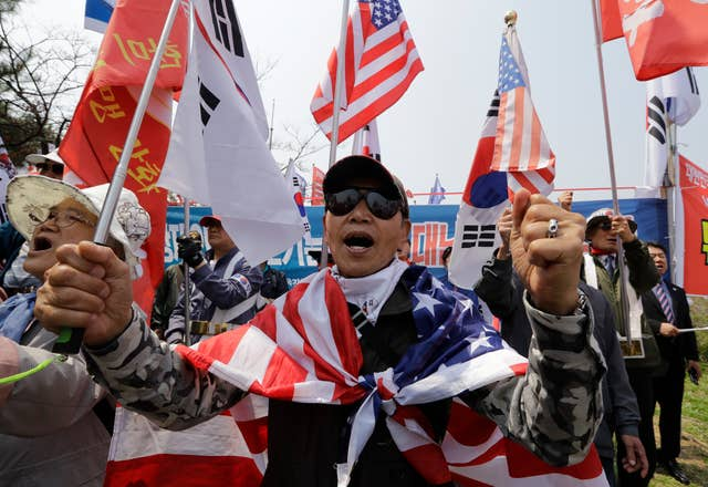 The historic meeting drew protesters in South Korea who shouted slogans and burnt flags (Lee Jin-man/AP)