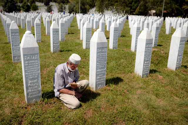 A man prays between grave stones in Potocari, near Srebrenica