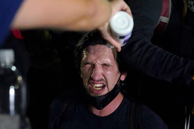A protester is helped after police used tear gas