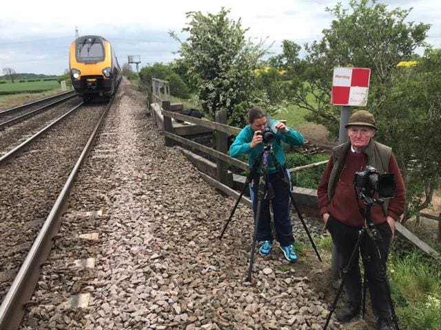 Two people standing next to a train line who trespassed on tracks to catch a close glimpse of Flying Scotsman