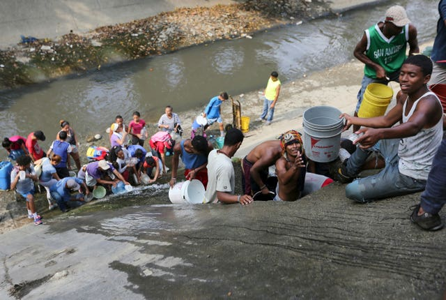 People collect water from an open pipe above the Guaire River