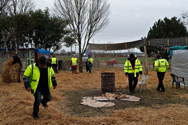Protestors wearing yellow vests stand in a makeshift camp on a roundabout near Senlis, north of Paris