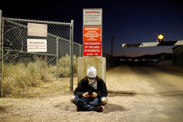 A man in a tinfoil hat sits near an entrance to the Nevada Test and Training Range near Area 51