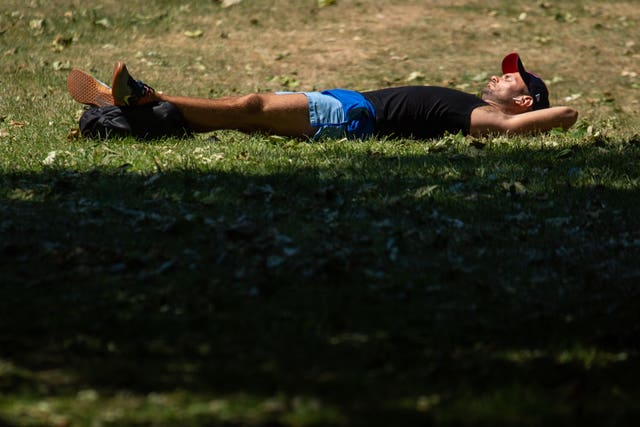 A man sunbathes in St James Park, London (Dominic Lipinski/PA)