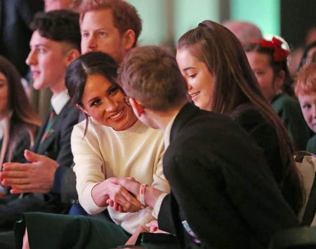 Prince Harry (second left) and Meghan Markle with guests during a visit at the Exhibition Centre in Lisburn