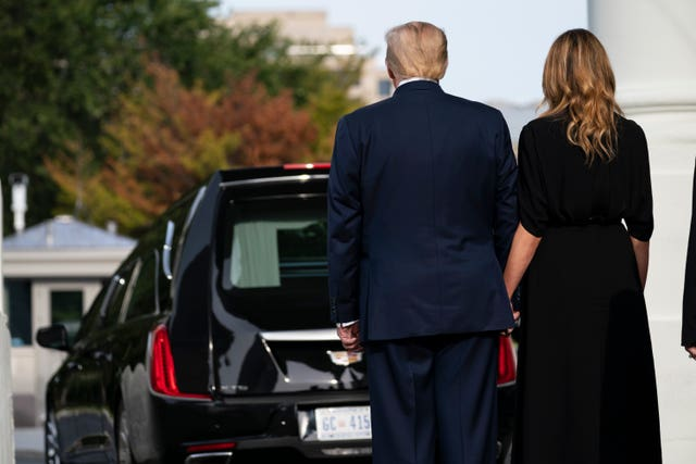 President Donald Trump and first lady Melania Trump watch as the coffin of Robert Trump leaves the White House (Evan Vucci/AP)