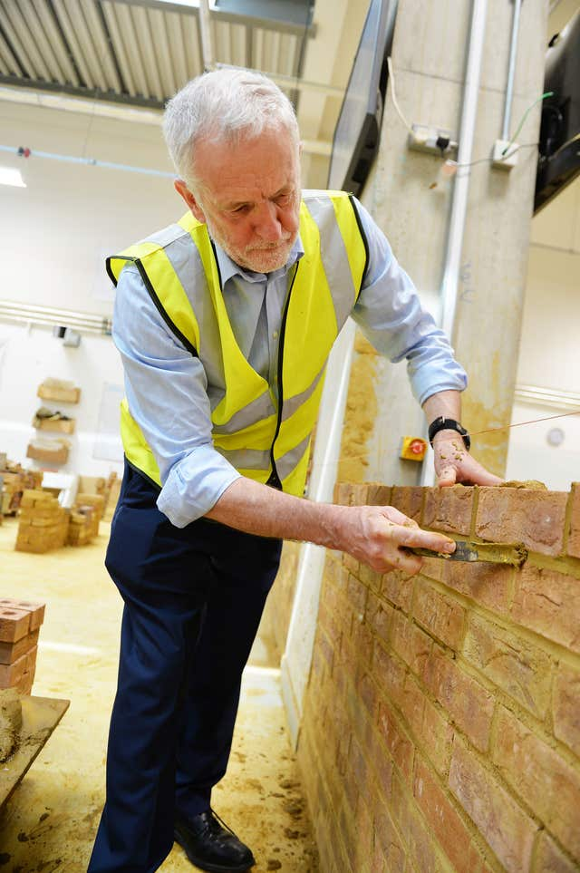 Labour leader Jeremy Corbyn gets hands on with a bricklaying project (John Stillwell/PA)