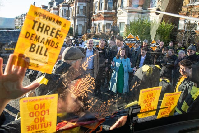 Liberal Democrat leader Jo Swinson speaks to Extinction Rebellion protesters dressed as bees after they glued themselves to the party's battle bus during a visit to Knights Youth Centre in London
